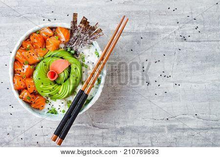 Hawaiian salmon poke bowl with seaweed avocado rose sesame seeds and scallions. Top view overhead flat lay copy space