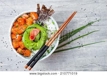 Hawaiian salmon poke bowl with seaweed avocado rose sesame seeds and scallions. Top view overhead flat lay