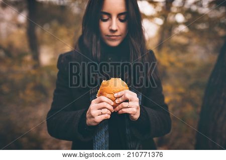 The concept of hunger and poverty. A roll or hamburger in the girls hands of a close-up.