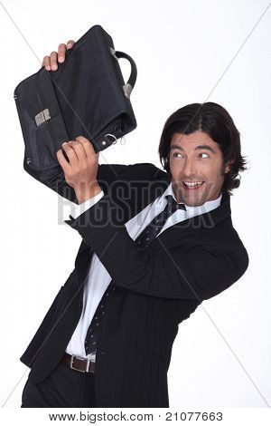 a business man is protecting his face with a briefcase, he looks amused