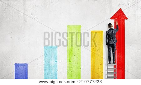 A businessman stands on a stepladder and draws with a paint roller several colorful chart columns. Build your success. Financial goals. Work for your dream.