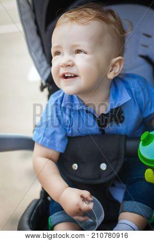 beautiful blonde boy sitting in pram, nice child resting in his pram after walking in park