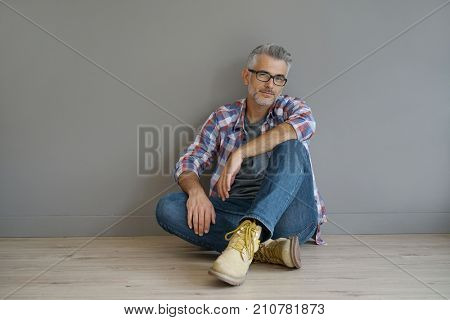 Trendy 40-year-old man sitting on floor, isolated