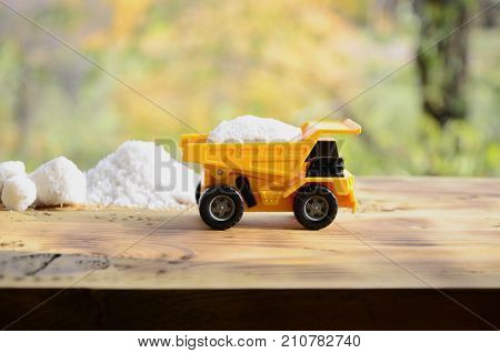 A Small Yellow Toy Truck Is Loaded With A Stone Of White Salt Next To A Pile Of Salt. A Car On A Woo