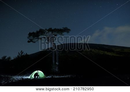 ETNA PARK, SICILY - OCTOBER 22, 2017: silhouette of a man going into the illuminated tent under a big pine, on background the profile of Etna Mount