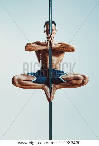 Young strong man pole dancing on blue and white background
