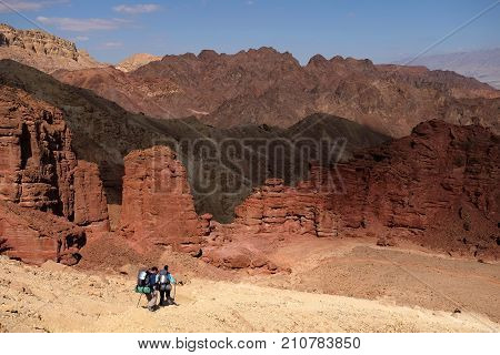 Unrecognized couple of hikers on scenic trail in Eilat Mountains Israel.