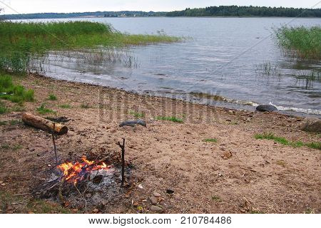 Landscape By The Water In Cloudy Weather, On The Bank Lit A Bonfire. Russia.