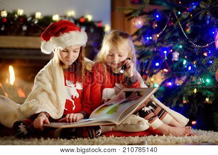 Happy Little Sisters Reading A Story Book Together By A Fireplace In A Cozy Dark Living Room On Chri