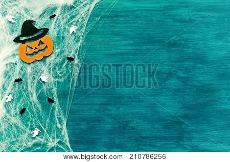 Halloween background. Spider web spiders and smiling jack decorations as symbols of Halloween on the green wooden background. Halloween background with Halloween festive objects as Halloween concept. Halloween still life
