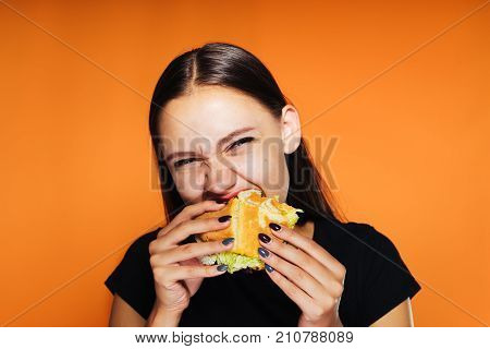girl eagerly eats an appetizing burger an orange background, isolated