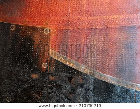 rusted burned red and black steel panels on a used soyuz entry landing capsule