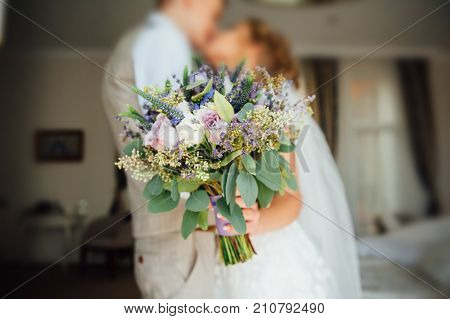 Bride and groom holding wedding bouquet together . Hug . beautiful hair. bride in a beautiful lace dress , the groom with a wooden butterfly