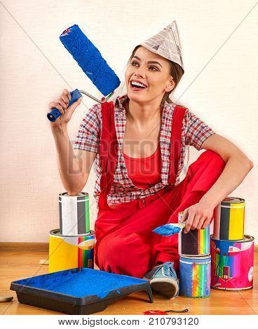 Repair home woman holding paint roller for wallpaper. Aggressive screaming girl in newspaper cap renovation apartment . Profitable loan for repairs.