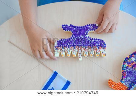 Boy with handmade nine-branched menorah at home