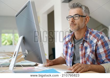 Web designer working in office on desktop computer