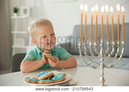 Jewish boy eating festive Hanukkah cookies at home