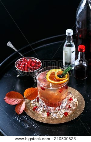 Red alcoholic cocktail with vodka and juice on a black background with pomagranate seeds, foodstyling, closeview.