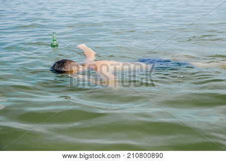 use of alcohol in water bodies. The guy drinks beer in the lake. Abuse of alcohol. drinking alcohol on the water