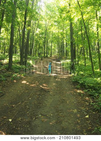 The Girl At The Age Of Seven Years Old Walking Along The Footpath In Summer Forest.