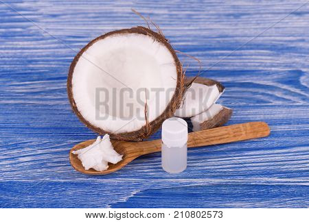 Half of coconut, pieces of coconut, coconut flakes and coconut glass jar on wooden background. Healthy food concept