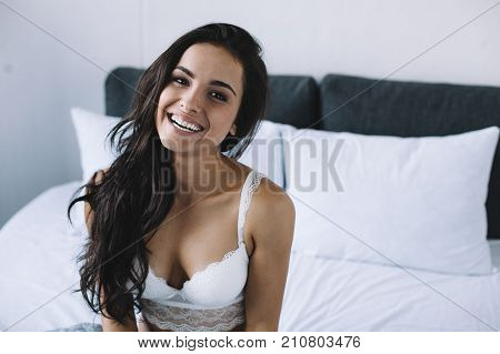 Close up of magnificent and cheerful young woman sitting at the edge of a big white and grey bed and smiling to the camera. She loks so lovely and impressive. She is very happy.