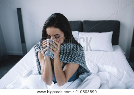This girl is sitting on the bed and drinking some hot tea from the cup. She got sick this morning and wants to recover as soon as possible. Young woman will take some medicine to feel better later this day. Close up.