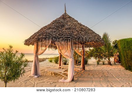 Beach lounge chairs at sunset at the shore of Indian ocean, Zanzibar, Tanzania.