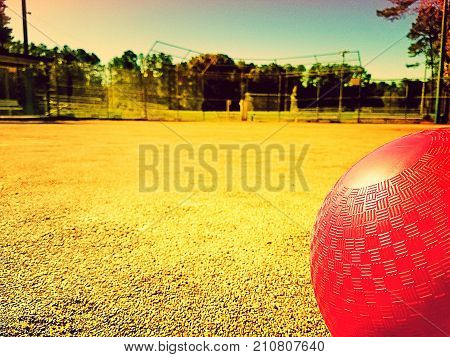 A playing field with a closeup of a red kick ball in forefront. Copy space.