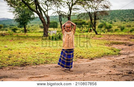 MAASAI MARA, KENYA - OCTOBER 17, 2014 : Young african girl posing in a Masai tribe village. The Maasai are a Nilotic ethnic group living in southern Kenya and northern Tanzania.