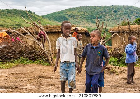 MASAI MARA, KENYA - OCTOBER 17, 2014: Two african boys from Masai tribe in their village. The Maasai are a Nilotic ethnic group living in southern Kenya and northern Tanzania.