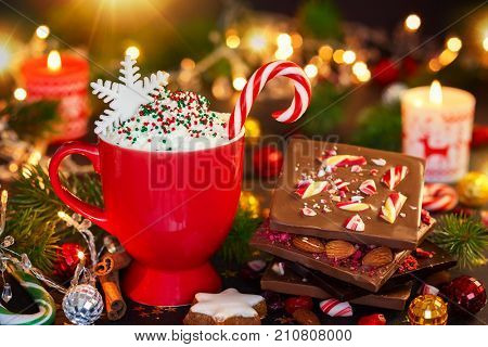 Christmas hot chocolate with cream, chocolate bark with peppermint,dried berries and nuts, Christmas cookies on the festive table.