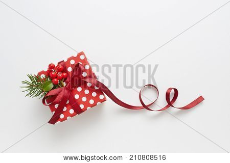 Christmas present wrapped with polka dot paper, and decorated with holly berries. Gift wrapped in polka dot paper with decorative red ribbon.