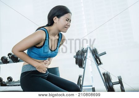 Young asian woman having pain in stomach. Asian sportswear woman having stomachache during her period.