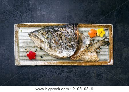 Traditional Japanese barbecue Kama Yaki salmon fish head as close-up on a plate