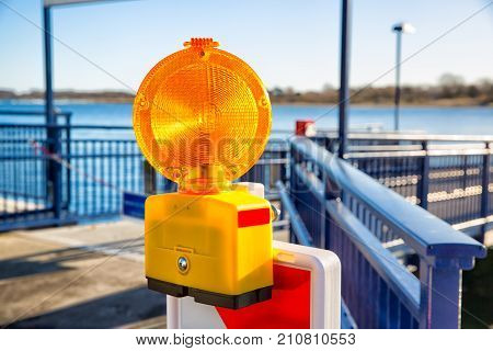 Signal alarm flashlight on guardrail of sea pier.
