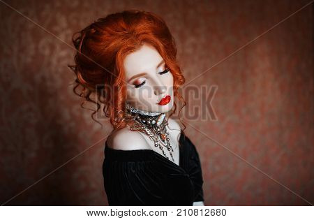 Renaissance woman is a vampire with pale skin and red hair in a black renaissance dress and a necklace on her neck. Renaissance girl with vampire claws and red lips. Gothic renaissance look. Renaissance outfit for halloween.