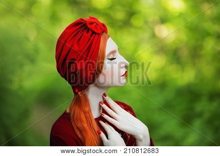 Glamour woman with pale skin and long red hair a red dress and a glamour turban on a summer background. Glamour girl with red nails. Glamour model. Glamour makeup