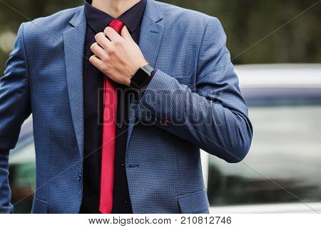 Successful business man in a dark business suit with a red tie against the background of a car. Stylish business man. Business professions. Business concept. Business vision. Successful business man in a classic suit