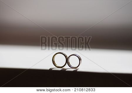 Wedding rings lie on a window on a dark white background. Gold wedding rings. Two rings on the windowsill. Rings on a white background