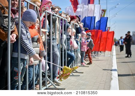 Yoshkar-Ola Russia - 9 May 2015 Photo of people standing outside the fence during the Victory Parade in Yoshkar-Ola Russia