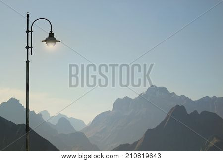 Beautiful and poetic view of Dolomites Alps in Italy with a street lamp detail