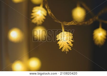 Blurred yellow christmas lights in shape of cones on dark background, low depth of focus.