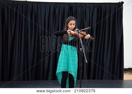 JOLIET, ILLINOIS / UNITED STATES - MARCH 23, 2016: A Drauden Point Middle School student plays her violin, in the school's annual talent show.