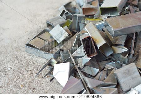 remnant of iron leftover of iron surplus on the gray concrete floor background.Iron,aluminium,metal,steel scrap can be melted recycle to create something new. helps reduce the problematic garbage.