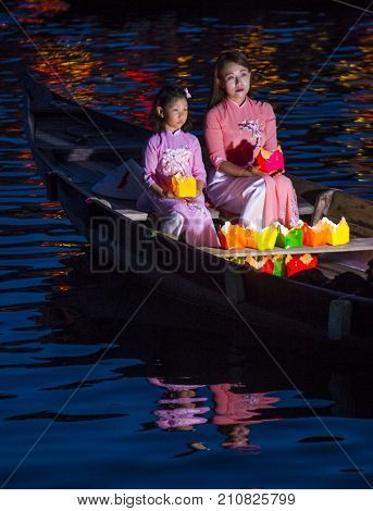 HOI AN VIETNAM - OCT 04 : Vietnamese mother and daughter holding Lanterns before droping them into the River in Hoi An Vietnam during the Hoi An Full Moon Lantern Festival on October 04 2017