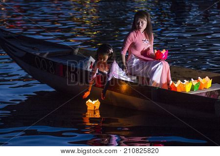 HOI AN VIETNAM - OCT 04 : Vietnamese mother and daughter dropping lanterns into the river in Hoi An Vietnam during the Hoi An Full Moon Lantern Festival on October 04 2017