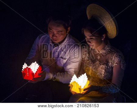 HOI AN VIETNAM - OCT 04 : Vietnamese couple holding lanterns before droping them into the river in Hoi An Vietnam during the Hoi An Full Moon Lantern Festival on October 04 2017