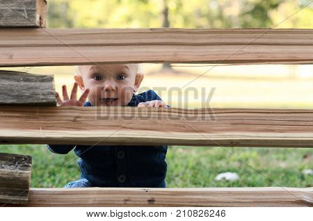 Small Boy Hiding Behind A Fence. Outdoor Activity Game Concept. Hide-and-seek Game.