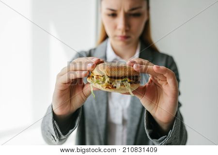 A young girl shows that she does not like a burger.Conceptual image of refusal from unhealthy eating. Fast food.